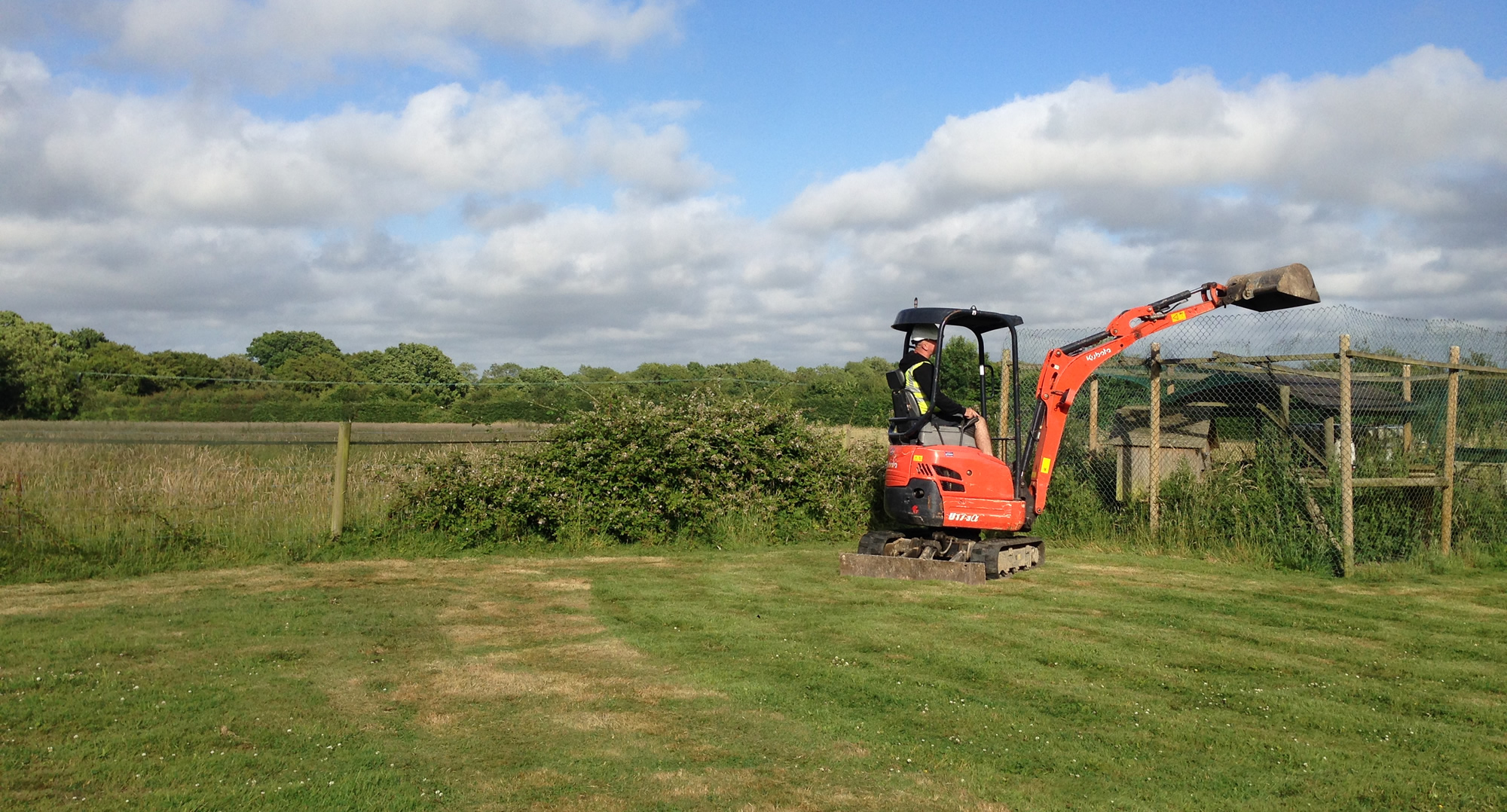jem with digger at fence in field
